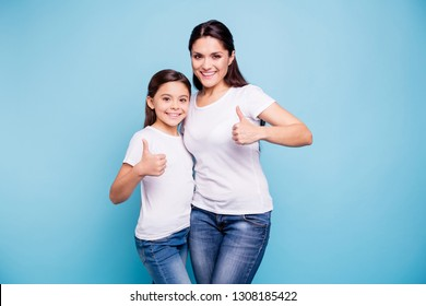Close up photo beautiful two people brown haired mom little daughter show thumbs in air recommending hugging best friends look similar wearing white t-shirts isolated bright blue background