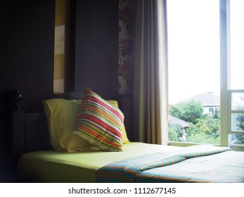 close up photo of a bed with stripes lines pillows in colourfu bed room equipped with large window under soft natural windows lighting
