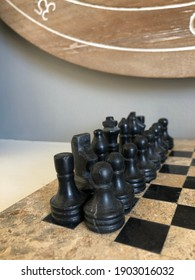 Up close photo of black hand carved coral chess pieces as a decoration on a white mantle.