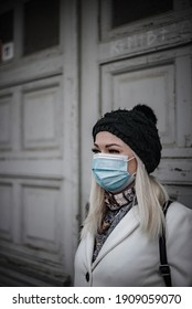 Close photo of blonde woman leaving the house and wearing face mask due to pandemic