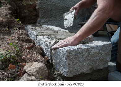 Close up photo of bricklayer with trowel, laying massive granite blocks as a part of garden wall. Detail of bricklayer's working hands.