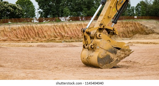 A close up photo of the bucket on an excavator at a construction site.