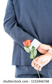 Close up photo of businessman in suit  holding red roses behind his back on white background