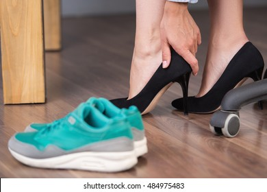 Close up photo of businesswoman legs. Tired businesswoman changing shoes while working day at her working place in office