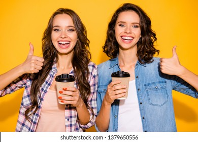Close up photo charming beautiful stylish ladies hold hand mug beverage choose decide recommend advise ads feedback good suggest demonstrate hairstyle checked jeans shirts isolated yellow background