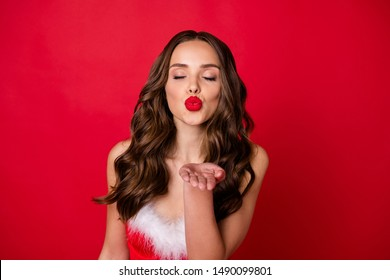 Close up photo of charming girl with her eyes closed sending air kisses having brunette wavy curly hair wearing dress isolated over red background