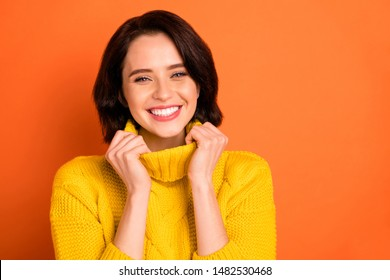 Close up photo of charming gorgeous woman being photographed wearing yellow sweater while isolated with orange background