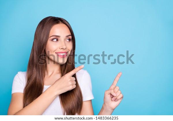 Fotografía de una encantadora mujer mirando el espacio de las copias, mostrando anuncios con pantalones blanco aislados sobre fondo azul