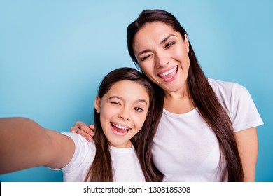 Close up photo cheer beautiful two people brown haired mum mom small little daughter make take selfies mouth laugh laughter flirty wink wear white t-shirts isolated bright blue background