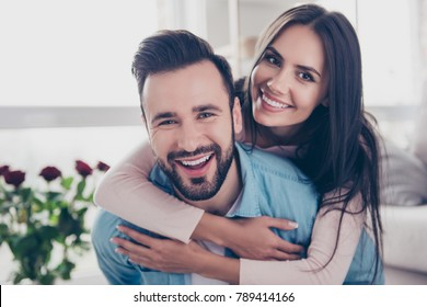 Close up photo of cheerful excited glad careless happy with toothy beaming smile brunette attractive woman and with stylish hairdo man, she is hugging him from the back