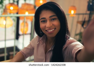 Close up photo of a cheerful young lady smiling to the camera while taking selfie. Lamps on the background