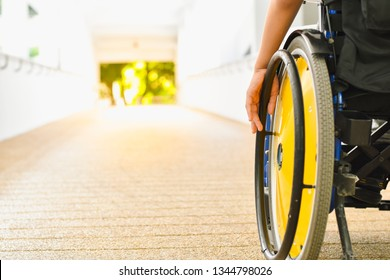 Close up photo of child sitting on the wheelchair in hospital walk way, His hand controlling the wheel, Life in the education age of children, Happy cerebral palsy kid concept.