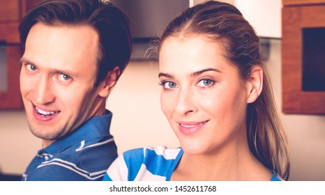 Close up photo of couple looking at camera while standing in kitchen, in home.