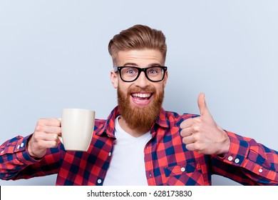 Close up photo of crazy happy smiling man in spectacles holding cup of tasty fresh coffee and showing thumb up