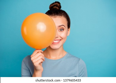 Close up photo of cute attractive lady hold hand orange ballons for anniversary hide feel content enjoy rejoice free time dressed cotton fashionable spring clothes isolated on blue background