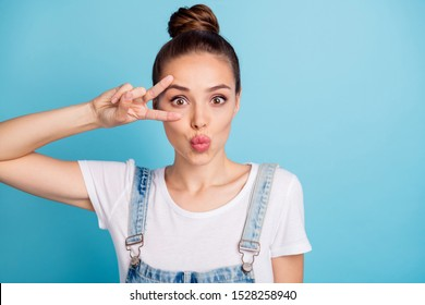 Close up photo of cute lady making v-signs near her face sending sir kisses wearing white t-shirt denim jeans overalls isolated over blue background