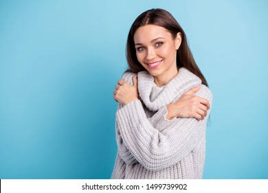 Close up photo of cute lovely girl hug herself enjoy have rest relax wear white knitted pullover sweater  with collar isolated over blue color background