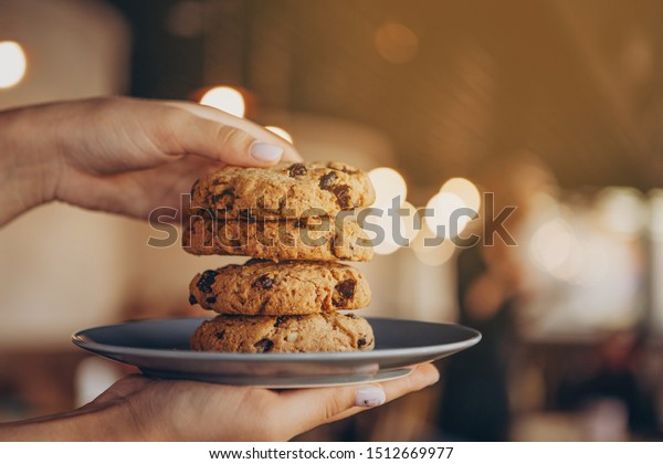close up photo of delicious and crunchy oatmeal cookies on the backdrop of a cozy restaurant or bakery interior, festive Christmas mood, 4 cookies lying on top of each other