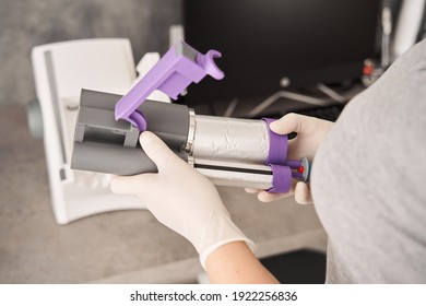 Close up photo of dental impression material mixing machine. Cropped view of the hands of female dentist holding part of impression material mixing machine before adjusting it into the machine