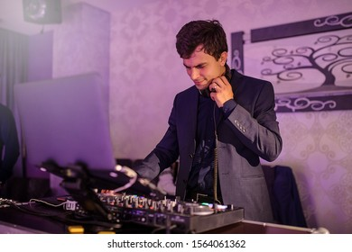 close up photo of a DJ in a suit mixing in the dark