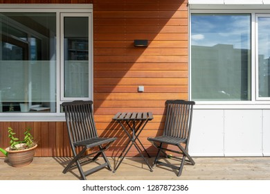 Close up photo of empty terrace with wooden furniture chair and table in modern house