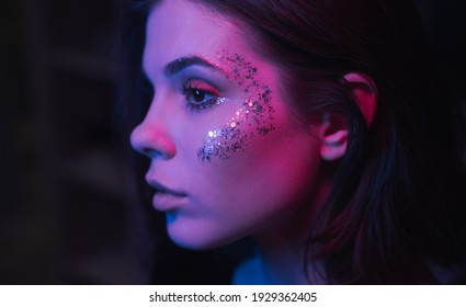 Close photo of face of woman with interesting make-up at night at party with purple light, focus on glitter.