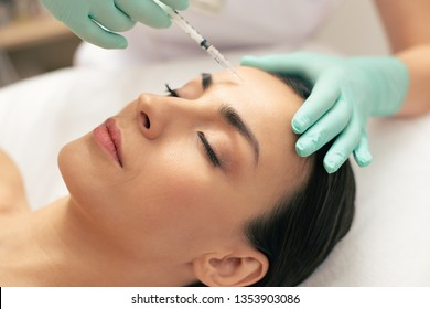 Close up photo of the face of young woman having her eyes closed and professional cosmetologist making an injection of hyaluronic acid