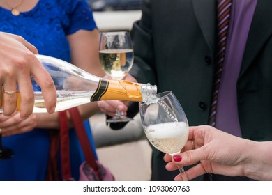 Close up photo of female hand that holding glass and man pouring champagne. Wedding party and celebration process. People in official and elegant clothing