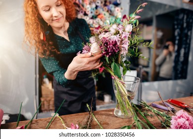 close up photo of female putting winsome flowers in vase in florist's shop.admiring beauty of flowers.showing flowers