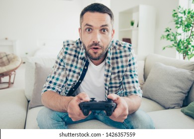 Close up photo of focused handsome mature guy hold hand have play station game pad dressed plaid denim jeans sit divan bearded amazed big apartment