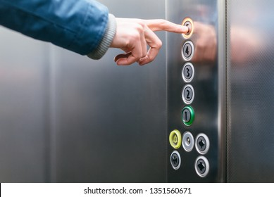 Close up photo of forefinger of adult man pressing the fifth floor button in the elevator/ use of the lift, place for copy space, human hand/ office and daily routine concept.