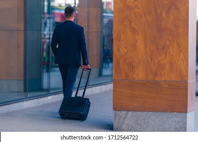 Close up photo a formal businessman dragging his suitcase, manbag, pull bag through a airport (station)