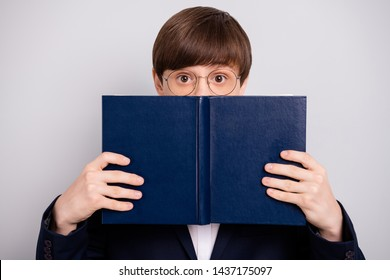 Close up photo funny funky astonished pupil secondary hold hand printed book library impressed new unexpected unbelievable information eyewear round eyeglasses blazer black isolated grey background