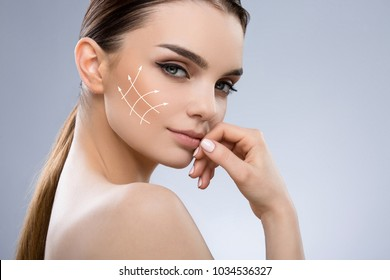 Close up photo of girl with dark brown hair, light big eyes and naked shoulders looking at camera and smiling slightly. Semi profile of model holding hand near face, beauty portrait with vectors