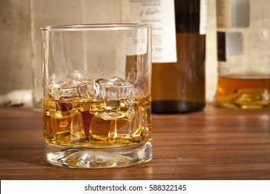 Close photo of a glass of dark alcohol on a wood table with bottles in the background.