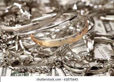 Close up photo of golden bracelet  and other jewelry at money background