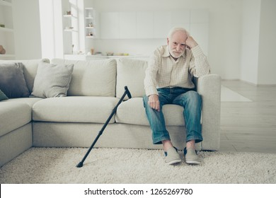 Close up photo of grey haired he his him grandpa with walking stick head lean on hand almost insane outraged about social program in country wearing casual checkered shirt outfit sitting on cozy divan
