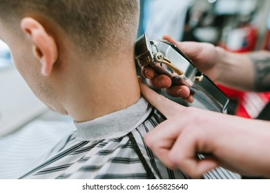 Close photo. Hand with clipper cuts hair on client's neck. Working with the clipper to create stylish hairstyles. Background. Barber concept. Copy space