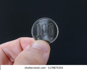 close up photo of hand holding 100 yen on the dark background. The Japan Financial concept.
