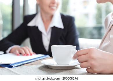 Close up photo of a hand of a woman holding a cup of coffee and her business partner, in a restaurant during business lunch, selective focus
