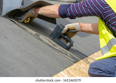 Close up photo hands with stapler of mature and professional working on roof top with stapler, attach special waterproof bitumen membrane. Man recovering rooftop of new modern building construction