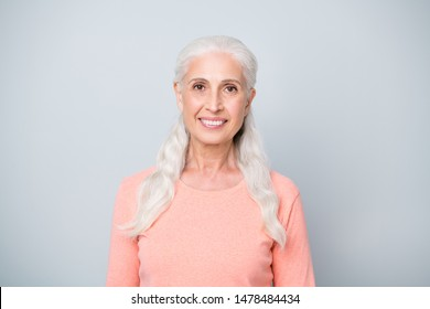 Close up photo headshot of charming attractive satisfied calm neutral granny having straight teeth wearing peach color jumper isolated grey background