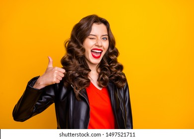 Close up photo of lady with red lips raising thumb up and winking eye wear leather jacket isolated yellow color background