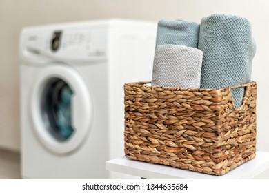 Close up photo of laundry basket with towels standing inside bright apartment light interior against blurred washing machine