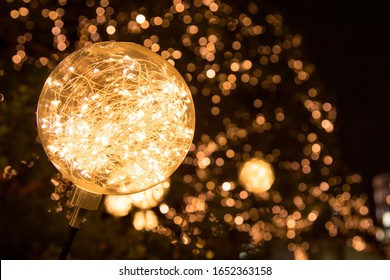 Up close photo of LED string lights inside clear ball with others creating a bokeh background