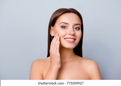 Close up photo of lovely attractive smiling woman with shiny smile, she is touching her cheek after using cream, isolated on grey background