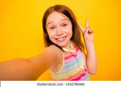 Close up photo of lovely kid making photo v-signs wearing stylish singlet isolated over yellow background