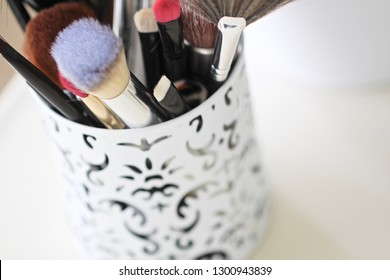 Close up photo of makeup brushes in ornate canister.