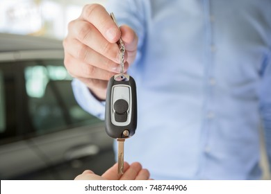 Close photo of male car dealer hand giving a car key to a female person hand. They are standing indoors in a showroom, with cars behind them
