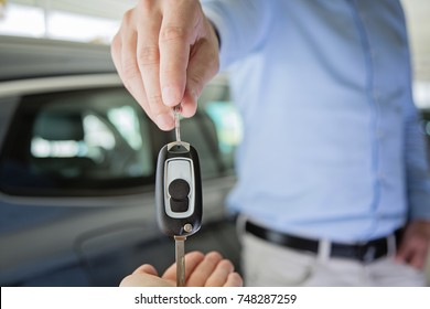 close up photo of a male hand giving car keys to female hand, indoors in a car dealership with a black car in the background, selective focus